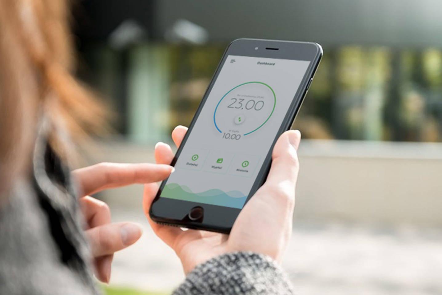 Osoba trzymająca w ręku telefon i korzystająca z mobilnej aplikacji finansowej blockchain