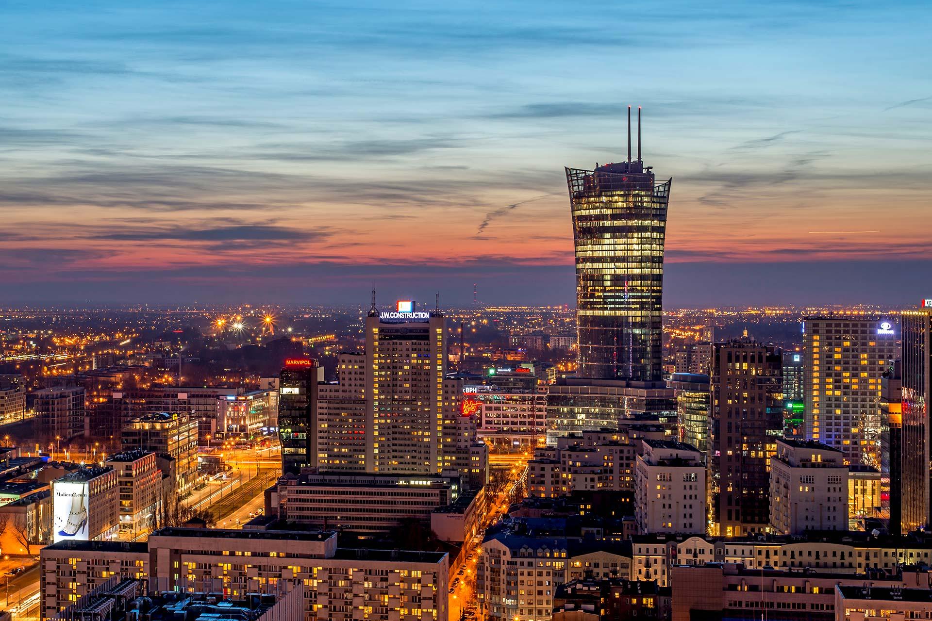 Budynki w centrum Warszawy sfotografowane na tle zachodzącego słońca