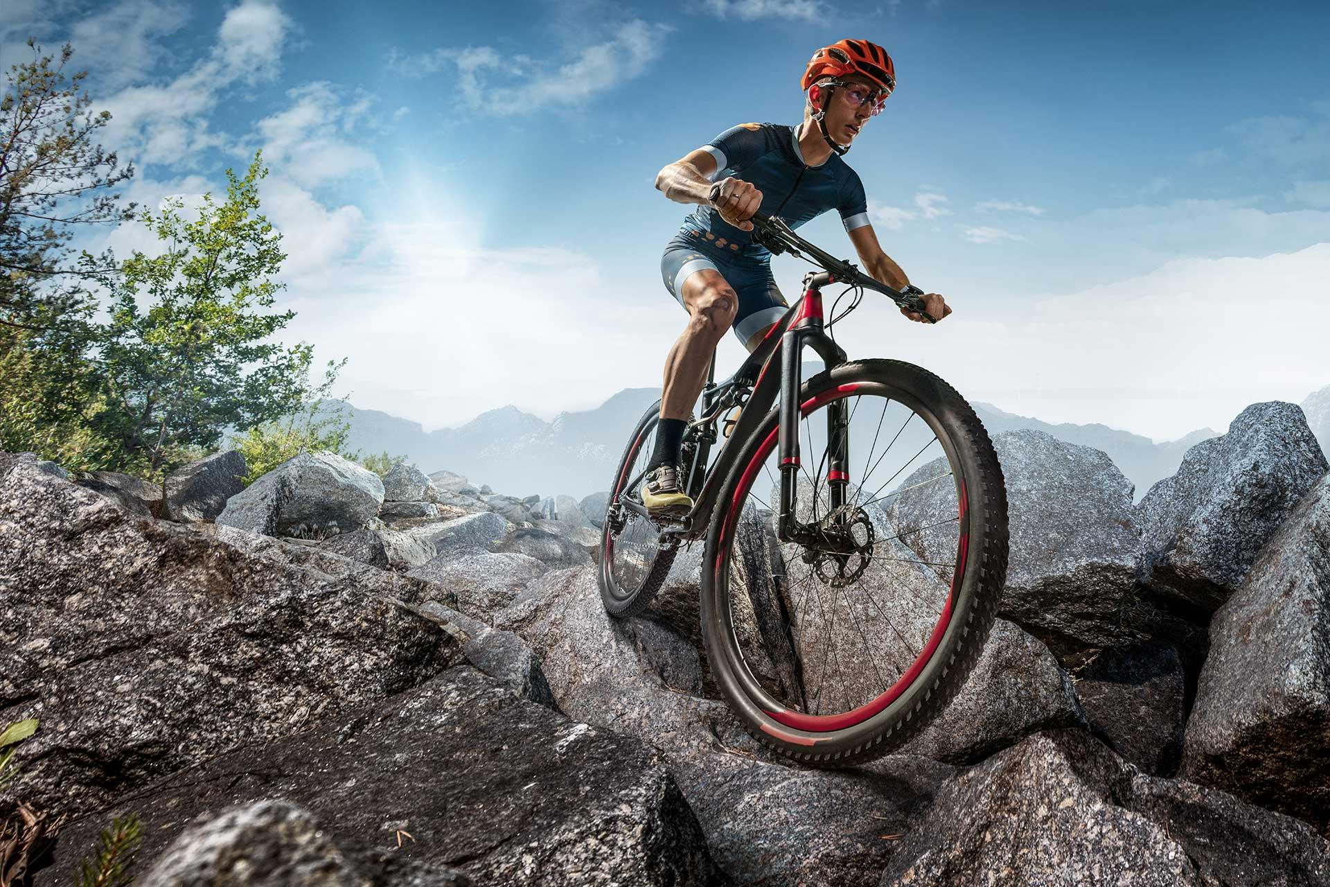 Mężczyzna w kasku i sportowym stroju jedzie po skalistej nawierzchni na rowerze górskim